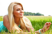 Woman relaxing outdoors looking happy and smiling — Stock Photo