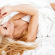 A woman lying at the end of the bed underneath the quilt and smiling. — Stock Photo #40603569