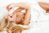 A woman lying at the end of the bed underneath the quilt and smiling. — Stock Photo