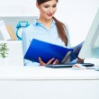 Portrait of young business woman working with paper at computer — Stock Photo