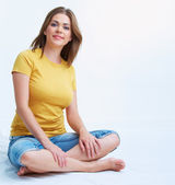 Smiling yong woman sitting on floor — Stock Photo