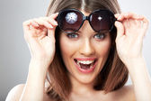 Toothy smiling young female model with sun glass. — Stock Photo
