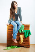 Young model seating at cupboard for clothes. — Stock Photo