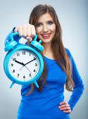 Mladý usmívající se žena v modrém držet hodinky. krásná usměvavá dívka — Stock fotografie
