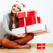 Young girl in Santa hat holding gifts — Stock Photo #34466915