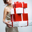 Young woman hold many red, white gift box . Female model isolat — Stock Photo #34467151