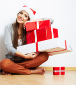 Young girl in Santa hat holding gifts — Stock Photo