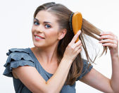 Woman combs hair — Stock Photo