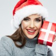 Portrait of woman in santa hat holding gift box — Stock Photo #34524917