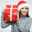 Portrait of woman in santa hat holding gift box — Stock Photo #34527187