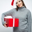Portrait of woman in santa hat holding gift box — Stock Photo #34527979