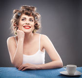Young woman with curlers and cup of coffee — Stock Photo