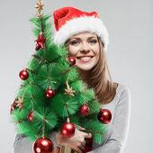 Femme au chapeau de santa holding arbre de Noël — Zdjęcie stockowe