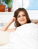 Smiling woman lying on sofa — Stock Photo