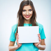 Teenager girl hold white blank paper. Young smiling woman show — Stock Photo