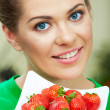 Smiling woman eating strawberry — Stock Photo