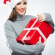 Portrait of woman in santa hat holding gift box — Stock Photo #34533715