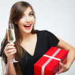 Woman holding gift box and glass of champagne — Stock Photo #34538785