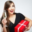 Woman holding gift box and glass of champagne — Stock Photo