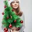 Woman in santa hat holding christmas tree — Stock Photo #34539023