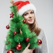 Woman in santa hat holding christmas tree — Stock Photo #34539243