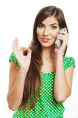 Portrait of woman using phone and showing ok sign — Stock Photo