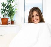 Woman on sofa with white blanket — Photo