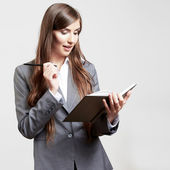 Business woman holding book and writing — Stock Photo