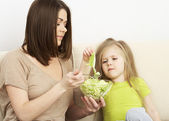 Mother feeds little girl — Stock Photo