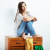 Young woman with clothes at home — Stock Photo