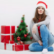 Woman in Santa hat sitting near christmas tree and gifts. — Stock Photo