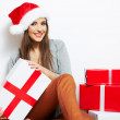 Woman in Christmas Santa hat holding gifts — Stock Photo