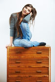 Young model seating at cupboard for clothes. — Stok fotoğraf