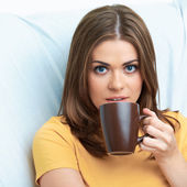 Portrait of woman seating on sofa with tea cup. — Stock Photo