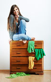Woman sitting on cupboard — Stok fotoğraf
