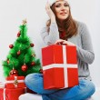 Santa woman seat near Christmas tree with christmas gift. — Stock Photo
