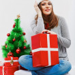Santa woman seat near Christmas tree with christmas gift. — Stockfoto #39677473