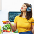 Girl drinking juice in kitchen and listen music. — Stock Photo #45914031