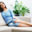 Portrait of young woman sitting on couch — Stock Photo