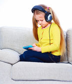Girl setting on sofa using tablet pc — Stock Photo