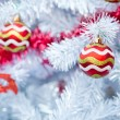 Christmas red balls and decorations on white Christmas tree — Stock Photo