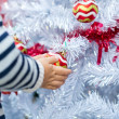 Child holds a Christmas red balls — Stock Photo