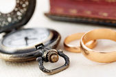 Pocket watch and wedding rings — Stock Photo