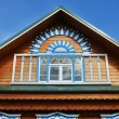 Wooden fretted roof with window on blue sky — Stock Photo