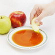 Hand dipping the piece of apple in honey as jewish new year sym - Stock Photo