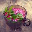 The cup of tea with rose petals and mint on old wooden backgroun — Stock Photo