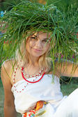 A beautiful woman wearing a crown of grass and Slavic costume. — Stock Photo