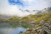 Alpine lake in the fog. — Foto de Stock