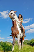 A young girl dressed as an Indian rides a paint horse — Stock Photo