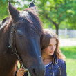 Portrait of a young girl with a horse. Focus on horses face - Stock Photo